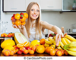 Happy blonde woman choosing fruits