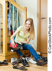 Happy blonde woman cleaning footwear