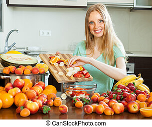Happy blonde woman cooking with ripe fruits