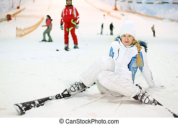 Happy blonde woman dressed in white sports clothes fells on ski in indoor ski