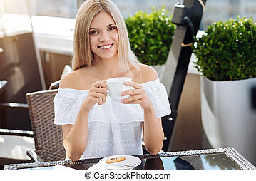 Happy blonde woman holding a cup