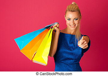 Happy blonde woman holding bunch of vibrant shopping bags after she bought a lot of things on sale.