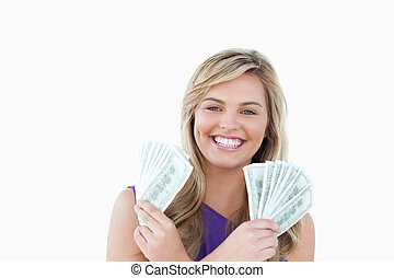 Happy blonde woman holding dollar notes