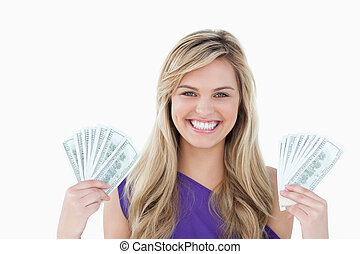 Happy blonde woman holding two fans of notes