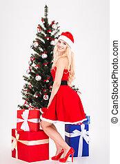 Happy blonde woman in santa cloth posing near christmas tree