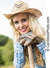 Happy blonde woman leaning on a shovel wearing gardening gloves