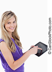 Happy blonde woman looking at the camera while touching her tablet computer