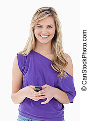 Happy blonde woman looking at the camera while holding her cellphone