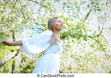 Happy blonde woman on a background of blooming spring garden with her hands raised to the sky