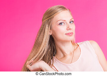 Happy Blonde Woman on pink background. Smiling Fashion Model...