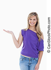 Happy blonde woman placing her palm up
