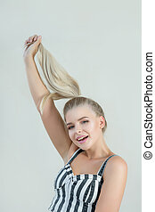 Happy blonde woman pulling her hair, posing in a grey background. Space for text