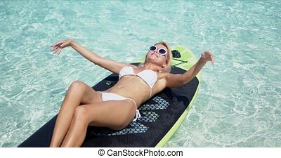 Happy blonde woman sunbathing on paddle board - Attractive ...