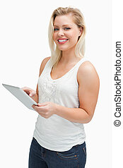 Happy blonde woman using her tablet computer