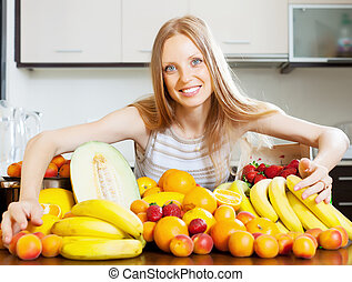 Happy blonde woman with heap of fruits