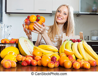 Happy blonde woman with heap of various fruits