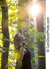Happy blonde young woman doing pilates exercise in a forest at sunrise with dumbells