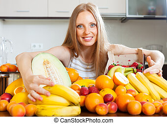 Happy blonde young woman with heap of fruits