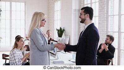 Happy boss handshake recognize promote mature female employee appreciate for good work results, proud middle aged businesswoman get corporate gratitude, personal respect applause in office concept