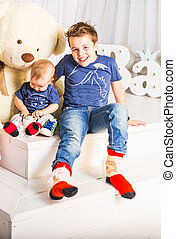 Happy boy and baby brother relaxing in white room