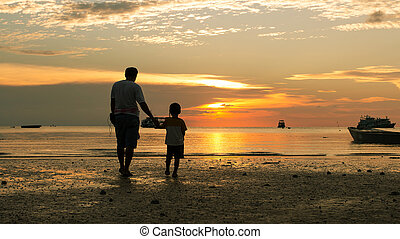 Happy boy and father walking on the beach sunset background
