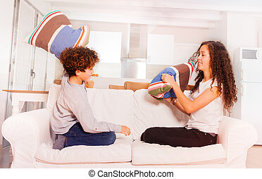 Happy boy and girl fighting with pillows at home