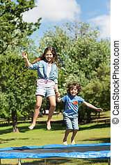 Happy boy and girl jumping high on trampoline in park