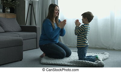 Happy boy and mother playing patty cake at home