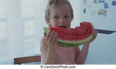 Happy boy appetizing eating red watermelon and juice flowing...