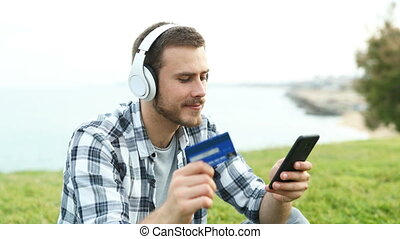 Happy boy buying music online with credit card and smart...