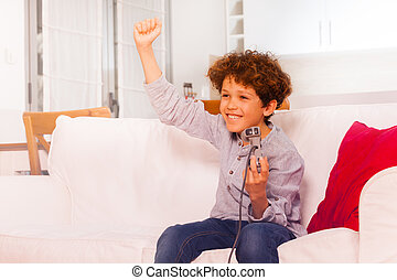 Happy boy celebrating victory, playing video games