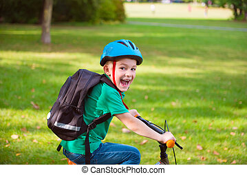 Happy boy cycling in park
