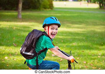 Happy boy cycling in park