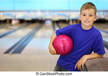 Happy boy dressed in blue T-shirt holds pink ball in bowling...