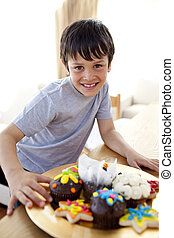 Happy boy eating colorful confectionery at home