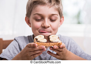 Happy boy eating delicious sandwich with banana and...