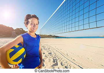 Happy boy getting ready for beach volleyball game