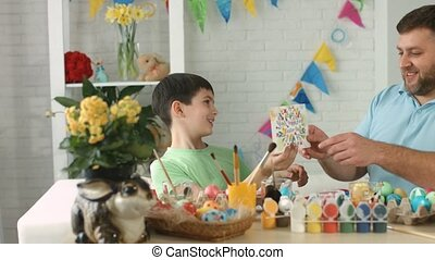 Happy boy gives his father a greeting card Happy Easter...