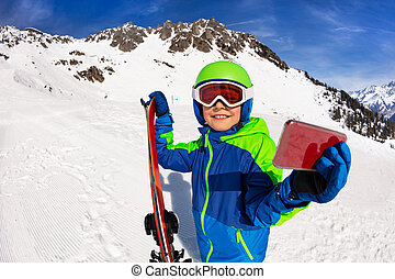 Happy boy hold ski taking picture with cell phone