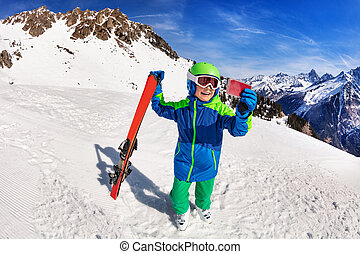 Happy boy hold ski taking picture with smartphone