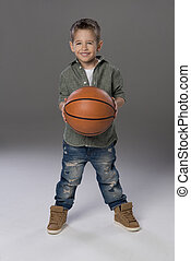 Happy boy holding basketball ball in hand