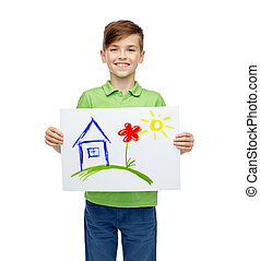 happy boy holding drawing or picture of home