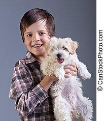 Happy boy holding his fluffy dog
