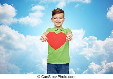 happy boy holding red heart shape