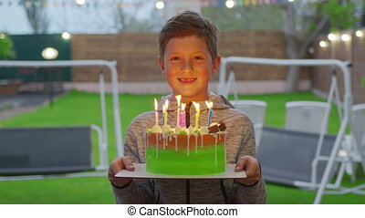 Happy boy holds a cake with burning candles. Birthday party.