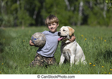 Happy boy hugging his dog breed Labrador. Best friends rest and have fun on vacation, play with soccer ball.