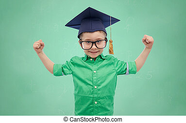 happy boy in bachelor hat showing power - childhood, school,...