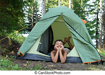 happy boy in camping tent in summer forest