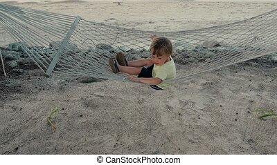 Happy boy in hammock on beach - Adorable toddler boy sitting...