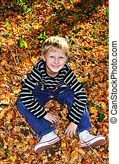 happy boy in sunny autumn forest